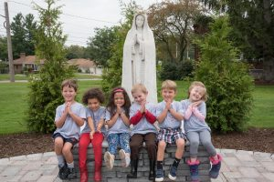 young students with prayer hands in front of Mary statue