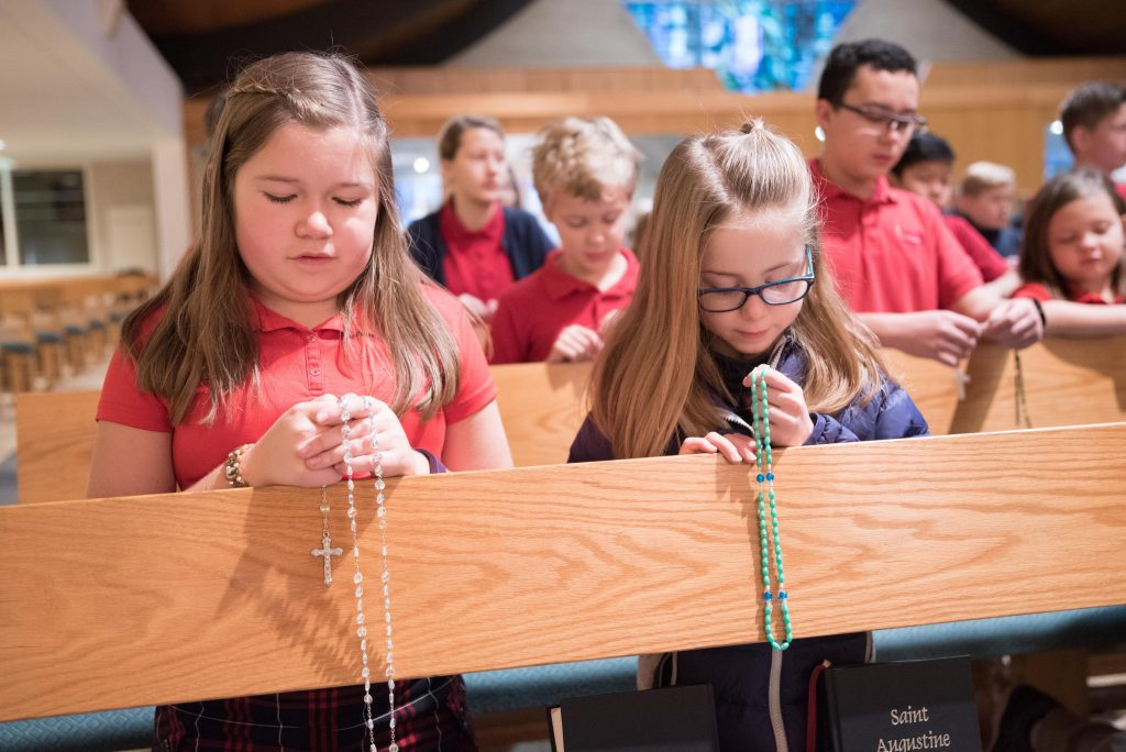 students knelt in pews praying rosary