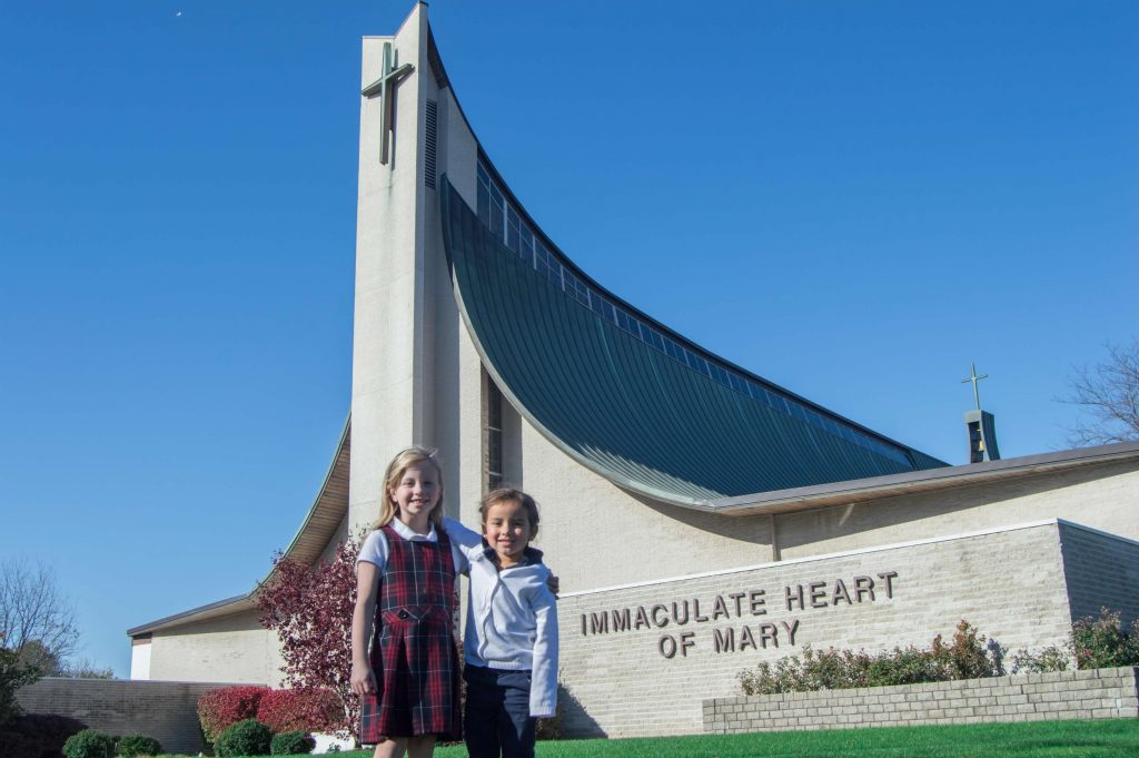 two female IHM students standing in front of IHM church